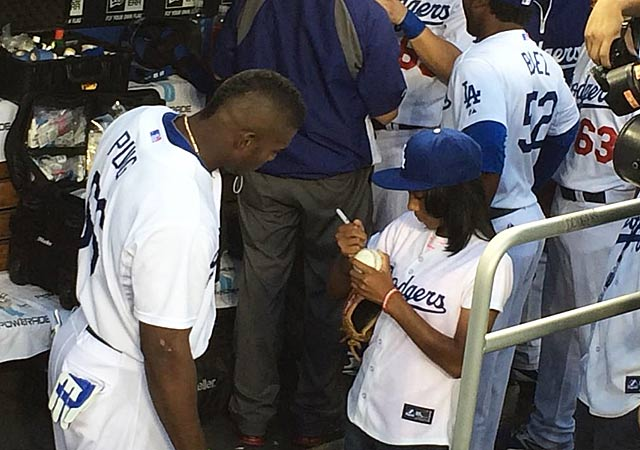 Mo'ne Davis signing an autograph for Dodgers star Yasiel Puig.